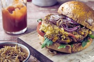 Freshly_made_insect_burger_with_fried_mealworms_and_salad_trimmings_served_with_tomato_ketchup_and_a_bowl_of_crispy_crunchy_worms_to_the_side_on_a_rustic_wooden_board