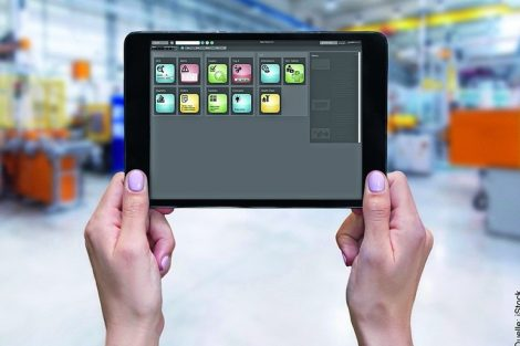 Horizontal_color_image_of_female_hands_holding_a_digital_tablet_in_a_modern_plastic_production_line._Ordering_on-line_from_injection_moulding_factory_on_a_touchscreen_tablet_computer._Large_factory,_industrial_machines,_robots_and_manufacturing_equipment_