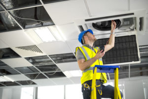 electrician_fitting_air_conditioning_to_office_interior
