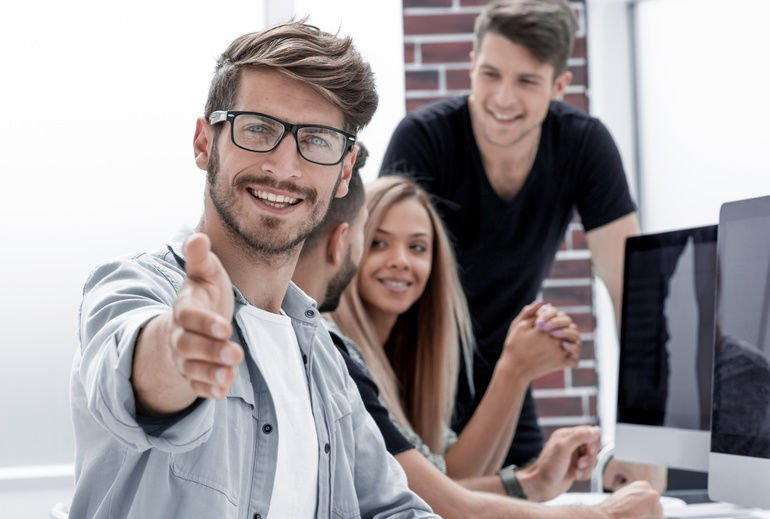 Handsome_young_man_looking_at_camera_and_smiling_while_his_colleagues_working_in_the_background