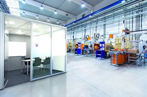 Horizontal_image_of_huge_new_modern_factory_with_robots_and_machines_producing_industrial_plastic_pieces_and_equipment._Wide_angle_view_of_futuristic_machines_standing_on_flooring_and_having_the_monopole_of_all_work,_taking_the_place_of_human_work._There_