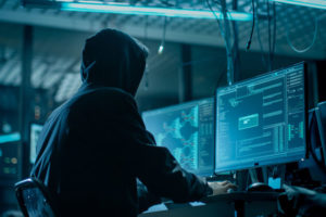 Shot_from_the_Back_to_Hooded_Hacker_Breaking_into_Corporate_Data_Servers_from_His_Underground_Hideout._Place_Has_Dark_Atmosphere,_Multiple_Displays,_Cables_Everywhere.