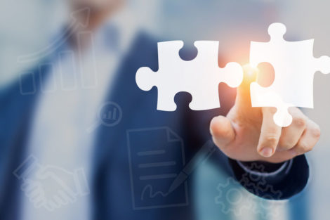 Mergers_and_acquisition_concept_with_consultant_touching_icons_of_puzzle_pieces_representing_the_merging_of_two_companies_or_joint_venture,_partnership