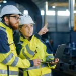 Portrait_of_Male_and_Female_Industrial_Engineers_in_Hard_Hats_Discuss_New_Project_while_Using_Laptop._They_Wear_Safety_Jackets.They_Work_at_the_Heavy_Industry_Manufacturing_Factory.