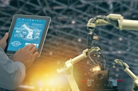 iot_industry_4.0_concept,industrial_engineer_using_software_(augmented,_virtual_reality)_in_tablet_to_monitoring_machine_in_real_time.Smart_factory_use_Automation_robot_arm_in_automotive_manufacturing
