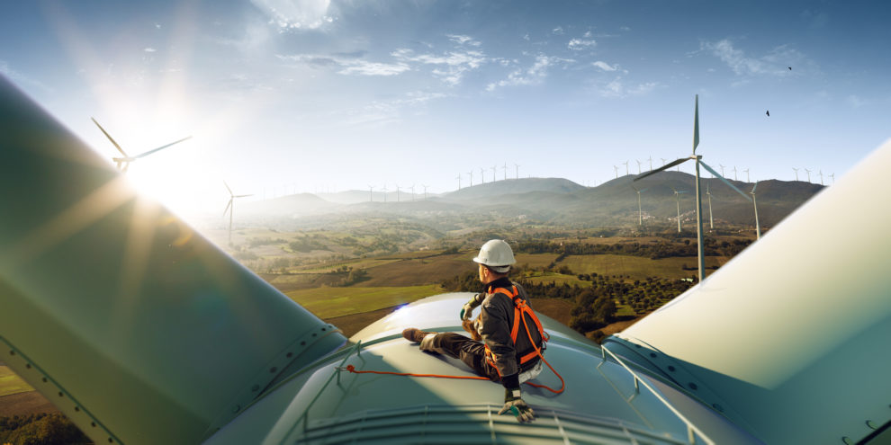 Happy_engineer_feel_success_after_good_work._He_standing_a_top_of_windmill_and_looking_beautiful_sunset_landscape