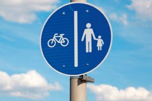 Bicycle_road_shared_with_pedestrians_sign_against_clear_blue_sky