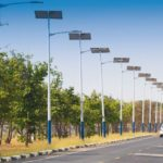 solar_street_light_lamp_post_led_with_panel_system_on_the_road_with_green_tree_and_blue_sky_for_background_energy_saving_concept.