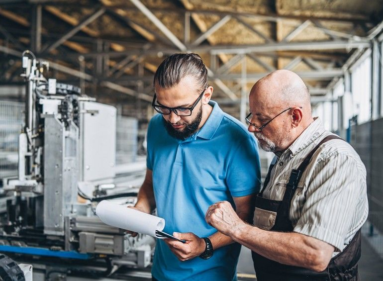 Two_people,_young_man_in_blue_t-shirt_with_papers_in_his_hand_and_an_older_man_in_glasses_with_gray_beard_and_bald_head,_working_in_factory_for_special_machine,_focused_on_work,_background_is_blurred,