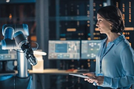 Female_Engineer_with_Tablet_Computer_Analyse_How_a_Futuristic_Robotic_Arm_Works_and_Moves_a_Metal_Object._High_Tech_Research_Laboratory_with_Modern_Equipment.
