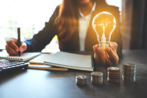 Businesswoman_holding_a_lightbulb_while_taking_note_on_notebook_with_coins_stack_on_table,_saving_energy_and_money_concept