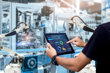 Smart_industry_control_concept.Hands_holding_tablet_on_blurred_automation_machine_as_background