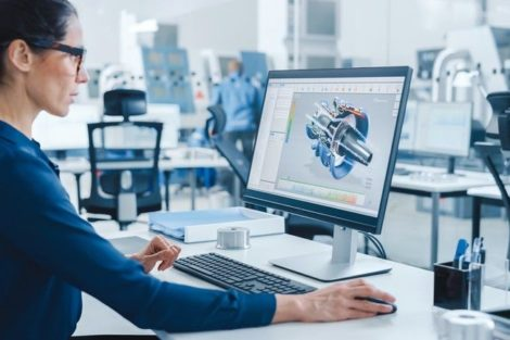 Industrial_female_Engineer_Working_on_a_Personal_Computer,_Screen_Shows_CAD_Software_with_3D_Prototype_of_Engine._Busy_Factory_with_Professional_Workers_High-Tech_Machinery