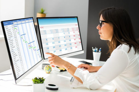 Employee_Working_On_Calendar_Schedule_And_Staff_Time_Sheet