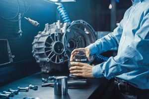 Professional_Automotive_Engineer_in_Glasses_is_Working_on_Transmission_Gears_in_a_High_Tech_Innovative_Laboratory_with_a_Computer_Screens.