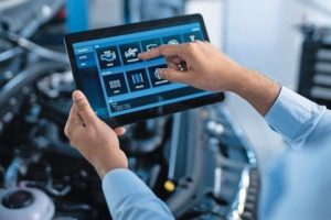 Car_Service_Manager_or_Mechanic_Uses_a_Tablet_Computer_with_a_Futuristic_Interactive_Diagnostics_Software._Specialist_Inspecting_the_Vehicle_in_Order_to_Find_Broken_Components_In_the_Engine_Bay.