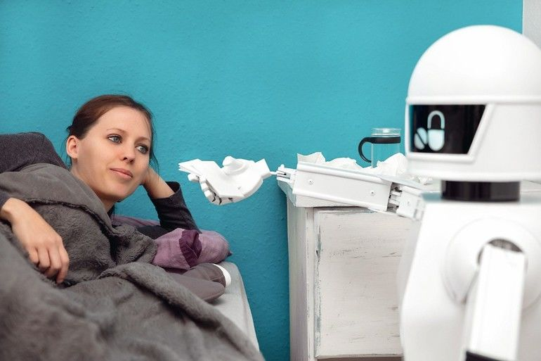 Medizinischer_Roboter_unterstützt_in_der_Krankenpflege,_autonomer_Roboter_bringt_einer_kranken_Patientin_Taschentücher