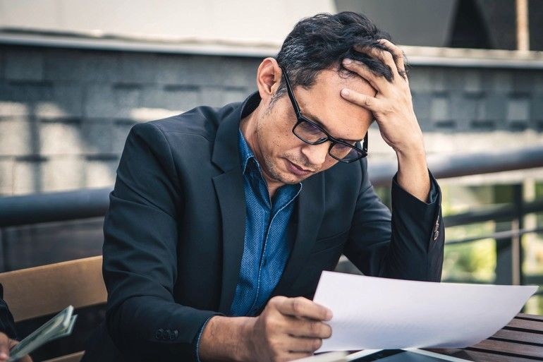 Senior_businessmen_are_worried_about_the_work_and_the_economic_downturn._Tired_and_worried_business_man_at_workplace_in_office_holding_his_head_on_hands.