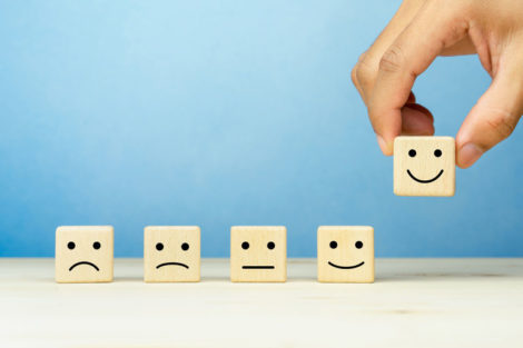 Customer_service_evaluation_and_satisfaction_survey_concepts._The_client's_hand_picked_the_happy_face_smile_face_symbol_on_wooden_cube,_copy_space