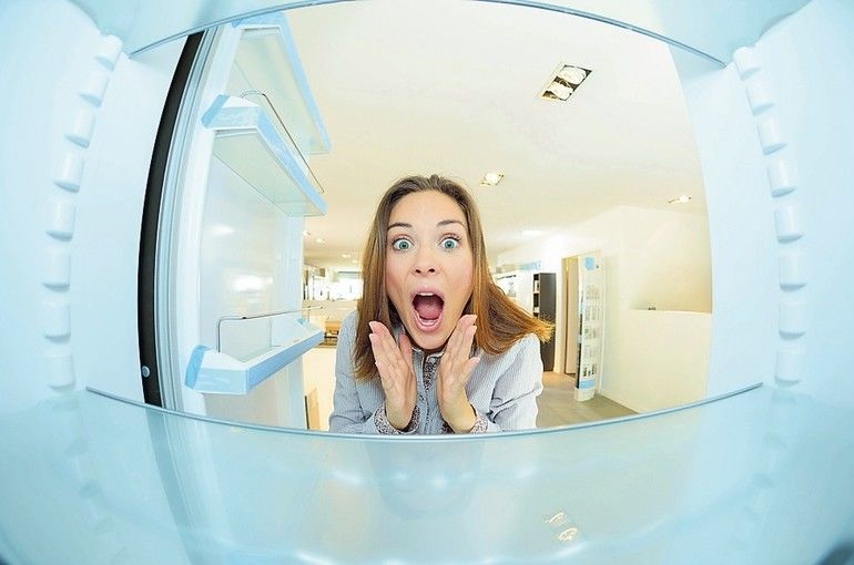Woman_with_shocked_expression_looking_inside_empty_fridge