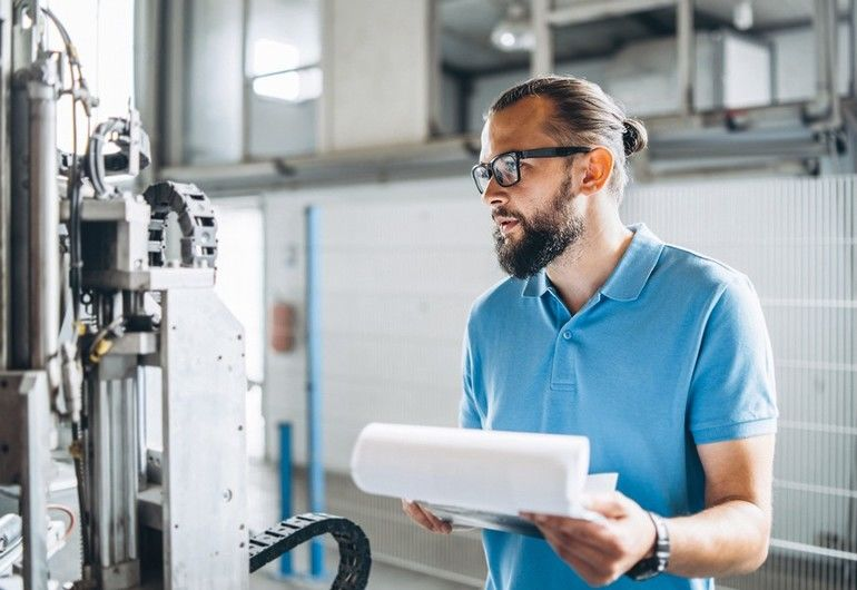 Young_engeneer_manager_with_beard_checking_manufactory,_workplace_and_machinery_on_big_factory