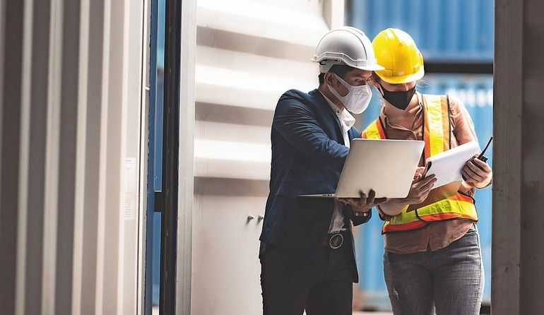 Business_executives_and_engineers_wear_medical_face_masks._While_inspecting_industrial_plants_and_warehouses_for_international_shipping_businesses_Concepts_of_import_and_export_via_airplanes_and_ships