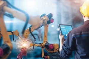 Engineer_check_and_control_welding_robotics_automatic_arms_machine_in_intelligent_factory_automotive_industrial_with_monitoring_system_software._Digital_manufacturing_operation._Industry_4.0