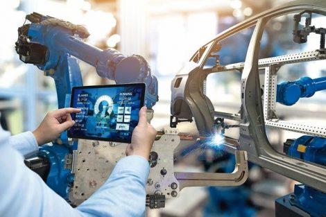 Engineer_hand_using_tablet_with_machine_real_time_monitoring_system_software._Automation_robot_arm_machine_in_smart_factory_automotive_industrial_Industry_4th_iot_,_digital_manufacturing_operation.