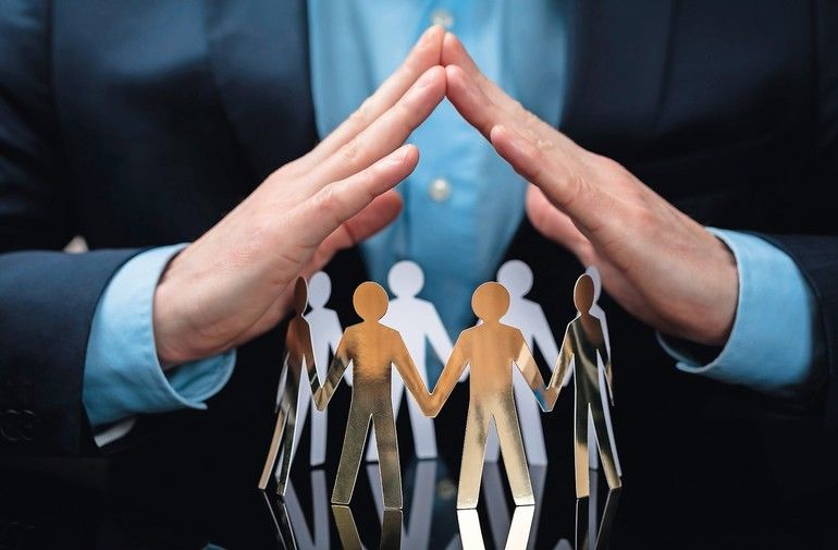 Close-up_Of_A_Businessperson's_Hand_Protecting_Paper_Cut_Out_People_On_Desk