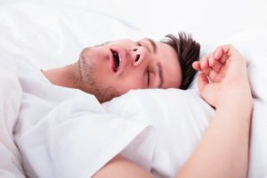 View_Of_Tired_Young_Man_Snoring_While_Deep_Sleeping_In_Bed