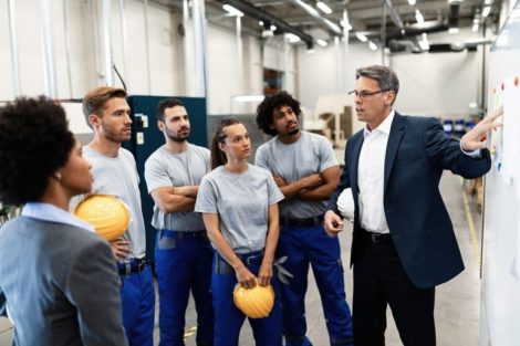 Mature_businessman_presenting_business_strategy_on_white_board_to_group_of_industrial_workers_in_a_factory._