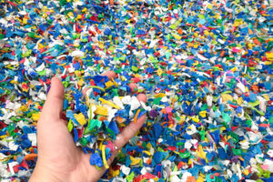 Hand_holding_Bottle_flake,PET_bottle_flake,Plastic_bottle_crushed,Small_pieces_of_cut_colorful_plastic_bottles