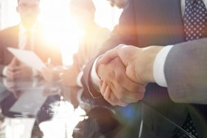 background_image_of_handshake_of_business_partners_in_conference_room