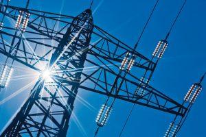 Ein_Hochspannungsmasten_für_Strom_vor_blauem_Himmel_und_Sonnenstrahlen