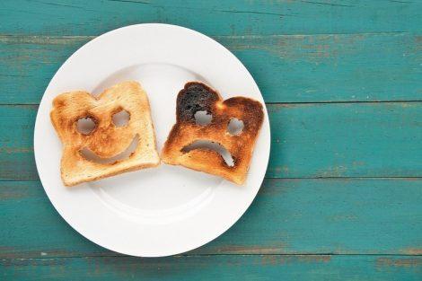 Flat_lay_view_of_two_slices_of_toasted_bread_in_a_white_plate._One_is_burned_and_one_is_well_done._Relationship_lifestyle_concept._copy_space
