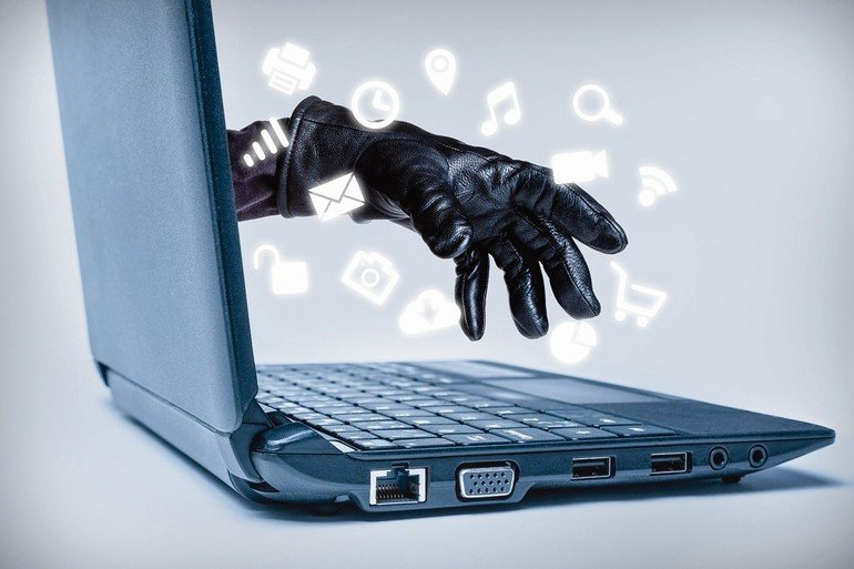 A_gloved_hand_reaching_out_through_a_laptop_with_common_media_icons_flowing,_signifying_a_cybercrime_or_Internet_theft_while_using_various_Internet_media.