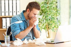 Portrait_of_a_sick_entrepreneur_blowing_in_a_wipe_at_office_with_a_lot_of_used_wipes_on_the_desk