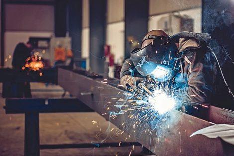 Industrial_Welder_With_Torch_and_Protective_Helmet_in_big_hall_welding_metal_profiles