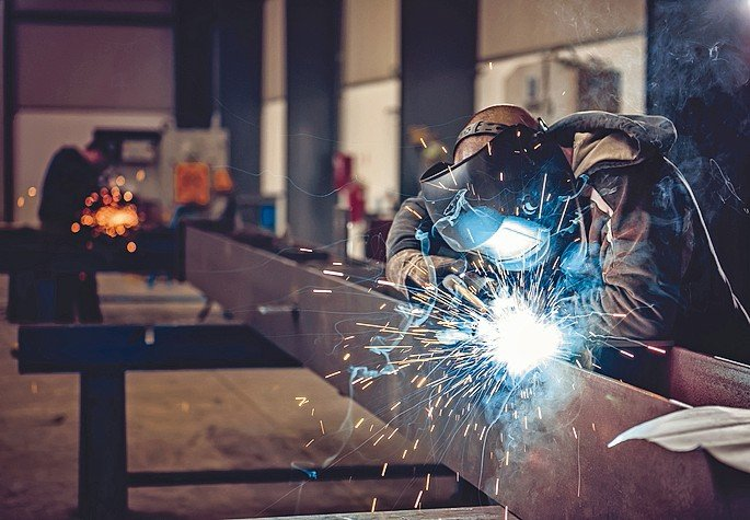 Industrial_Welder_With_Torch_and_Protective_Helmet_in_big_hall_welding_metal_profiles