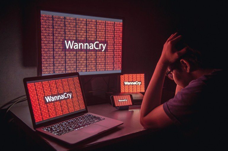 Young_Asian_male_frustrated,_confused_and_headache_by_WannaCry_ransomware_attack_on_desktop_screen,_notebook_and_smartphone,_cyber_attack_internet_security_concept