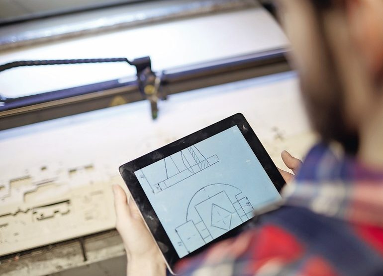 High_angle_shot_of_factory_worker_using_digital_tablet_to_operate_laser_cutting_machine_in_workshop