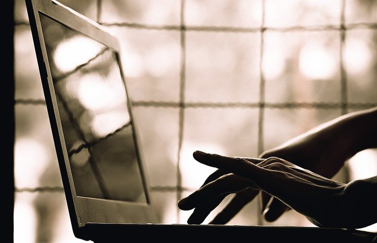 silhouette_black_and_white_of_anonymous_hacker_typing_on_keyboard_of_laptop_for_remotely_hacking_and_receiving_personal_information_near_window,_Payment_Security_Concept