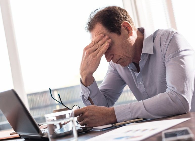 Stressed_businessman_sitting_in_office_with_hand_on_forehead