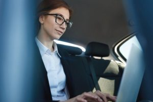 Mid-age_business_woman_working_while_being_in_the_car