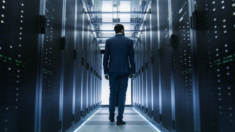 Following_Shot_of_IT_Engineer_Walking_Through_Data_Center_with_Rows_of_Working_Rack_Servers_on_Both_Sides.