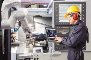 Engineer_using_laptop_computer_for_maintenance_automatic_robotic_arm_with_CNC_machine_in_smart_factory._Industry_4.0_concept