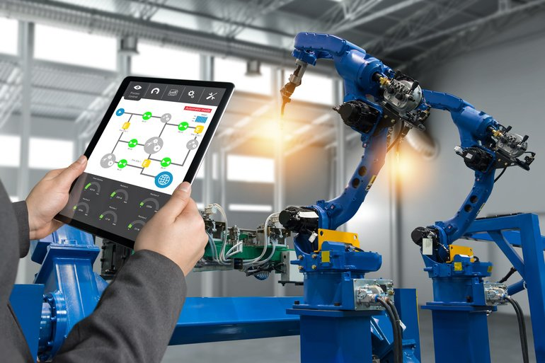 Engineer_hand_using_tablet,_heavy_automation_robot_arm_machine_in_smart_factory_industrial_with_tablet_real_time_process_control_monitoring_system_application._Industry_4th_iot_concept.