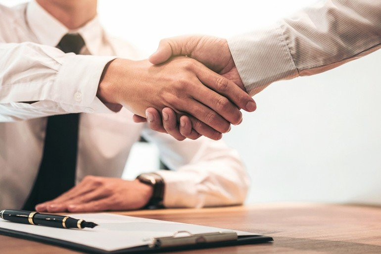 Real_estate_broker_agent_and_customer_shaking_hands_after_signing_contract_documents_for_realty_purchase,_Bank_employees_congratulate,_Concept_mortgage_loan_approval.