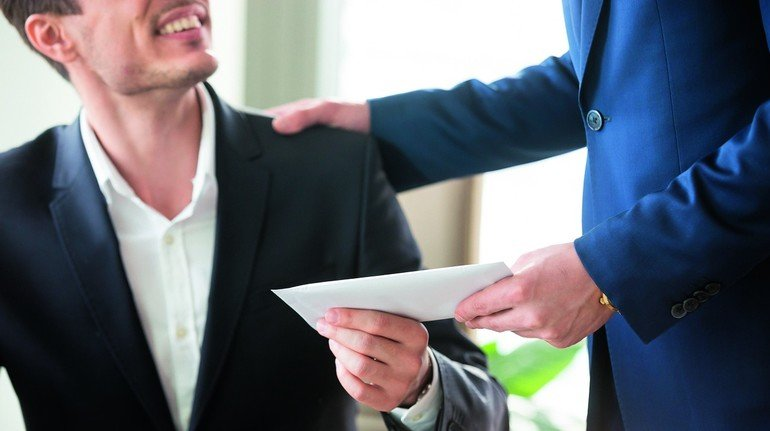 Company_leader_giving_money_bonus_in_paper_envelope_to_happy_smiling_office_worker,_congratulating_employee_with_increasing_of_salary_or_promotion,_thanking_for_successes_in_work._Close_up_concept