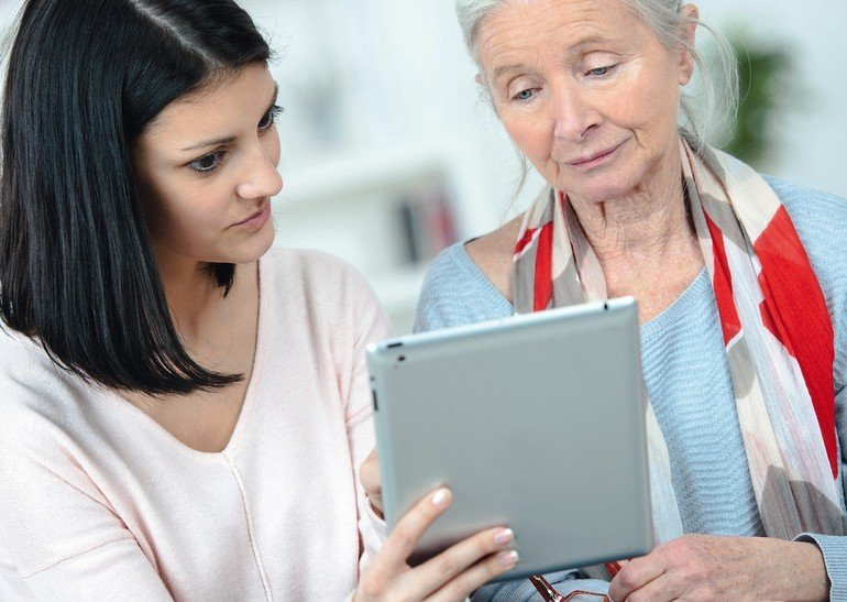 young_woman_helping_her_grandmother_using_a_tablet